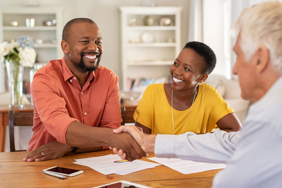 couple shakes hands with financial planner